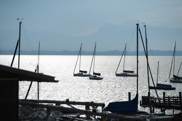 Sailing boats are moored at a small harbour on lake Chiemsee in Prien am Chiemsee