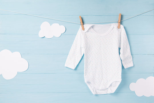 Baby clothes and white clouds on a clothesline, blue background