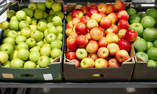 Boxes with ripe red and green apples on shelves of supermarket