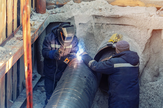 Welder welding water or gas steel pipeline with assistant worker in trench. City underground utilitites renewal and replacemen