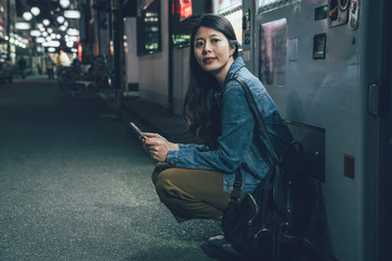 Girl backpacker using smartphone body leaning on beverage vending machine on dark street at night in city. young asian woman waiting holding cellphone kneeling down on quiet road in osaka japan.