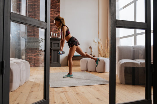 Active fit woman exercising with barbells at home