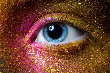 beautiful female eye with yellow, gold and purple, paint on skin, space and stars. Creative makeup close-up. macro.