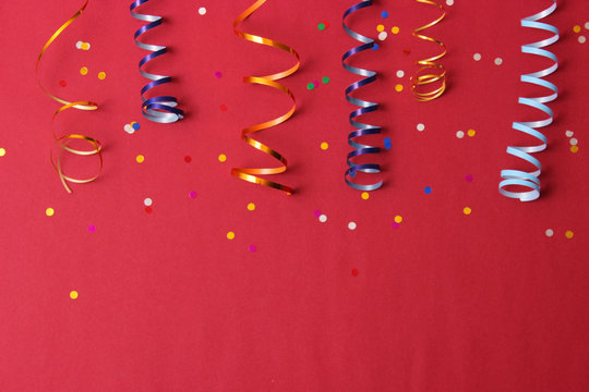 Festive background of ribbons and confetti on a colored background top view.