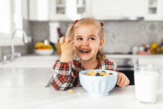Beautiful little girl having breakfast with cereal, milk and blueberry in kitchen