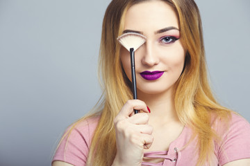 Wall Mural - portrait of a beautiful young girl in a studio, woman covers the eye with makeup brush, cosmetics and natural beauty concept