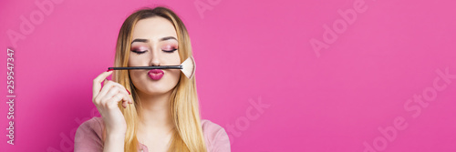 Wall mural funny portrait of a beautiful young girl with makeup brush in a studio, woman face, cosmetics and natural beauty concept