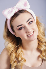 Wall Mural - soft studio portrait of a happy young woman with fluffy soft hoop on head that picks hair, fresh girl face with make up, the concept of natural beauty, body care, cosmetics