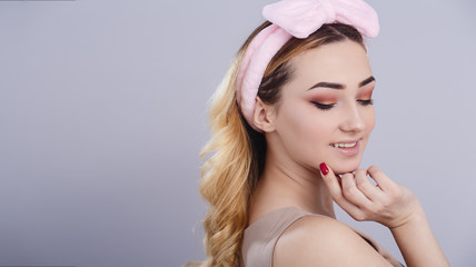 Wall Mural - soft studio portrait of a beautiful young woman with fluffy soft hoop on head that picks hair, fresh girl face with make up, the concept of natural beauty, body care, cosmetics