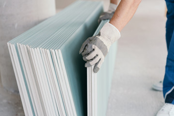 Builder taking a sheet of chip board cladding