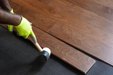 Worker installing hardwood fllors / Home improvement concept, selective focus