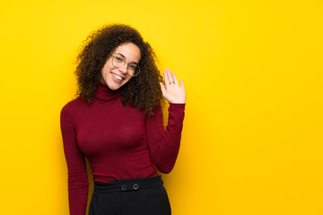 Dominican woman with turtleneck sweater saluting with hand with happy expression