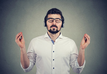 man in headphones with closed eyes listening to music and meditating