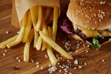 salt, french fries and delicious burger with meat on wooden surface