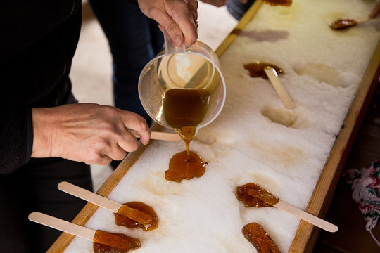 Making maple candy on snow in a maple sugar camp in New Brunswick
