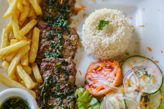 churrasco steak with chimichurri sauce served on plate with frites, rice and vegetables. Typical Argentinan food. Beef Steak