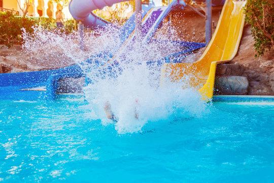 Senior woman having fun on water slide in hotel aquapark