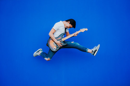 young man jumping with electric guitar on blue background