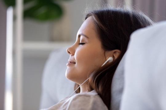 Side view closeup face of woman wearing earphones enjoy music