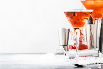 Classic alcoholic cocktail Manhattan with american bourbon, red vermouth, bitter, ice and cocktail cherry in glass, tools, gray bar counter background, copy space, selective focus