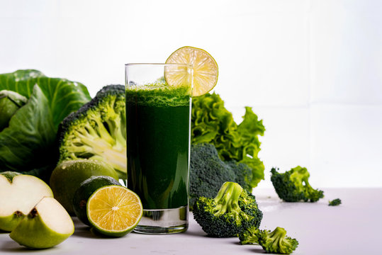 Green smoothie with apple and cauliflower on white wooden background. Raw food and drink. Copy space