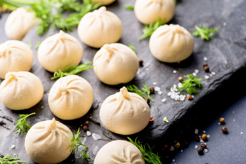 frozen khinkali and dumplings on a dark background with ingredients and spices. Semi-finished products