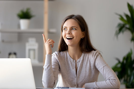 Young woman sitting at desk feels excited with good idea
