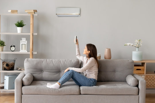 Young smiling woman sitting on couch switching on air conditioner