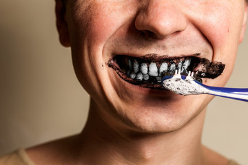 young man brushing white teeth with a black tooth paste with active charcoal, and black tooth brush