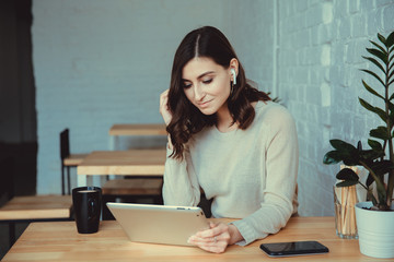 Young woman with airpods scrolling in her tablet, smartphone on the table. Working in cafe.