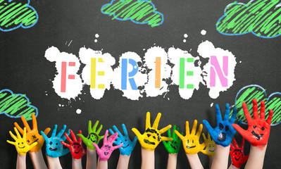 """angemalte Kinderhände vor Kreidetafel mit dem Wort """"Ferien"""""""