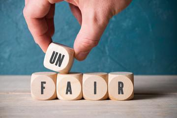 """Hand verändert Wort """"unfair"""" zu """"fair"""" durch Wegnahme eines Würfels"""