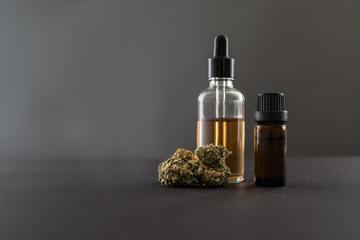 Medizinisches Cannabis und Cannabis Öl in Fläschchen grauer Hintergrund
