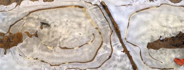Obraz zamarznięta kałuża na piaszczystej drodze, odcienie brązu, czerwony liść 1 - fototapety do salonu