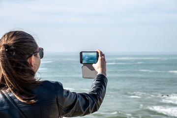 Jolie fille adolescent prend des photos de la mer avec le téléphone portable