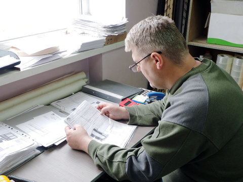 man looking at paper in glasses.