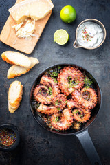 Traditional Spanish octopus braised cooked with aioli and baguette in wine sauce as top view in a cast-iron saucepan