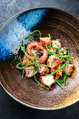Traditional French octopus braised cooked with Salicornia, lemon curd and spice as top view in a modern design Japanese bowl