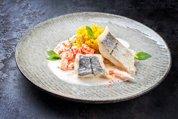 Fried haddock filet with saffron rice and shell prawns in crab sauce as closeup on a modern design plate