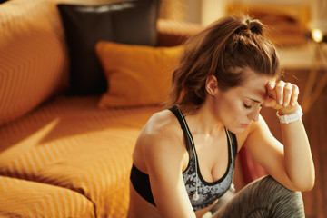 stressed fit woman with headphones at modern home