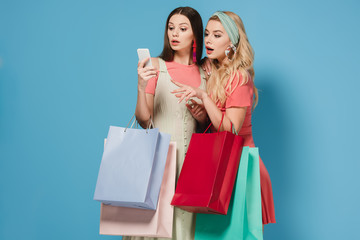 surprised brunette and blonde women in dresses holding shopping bags and using smartphone