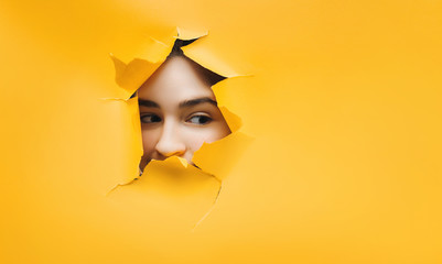 Surprised teenage funny girl face. Cute attractive girl looking through hole. Copy space for advertising, to insert text or slogan. Discount, sale. Wall mural