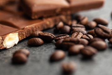 Coffee beans and dark chocolate glaze on gray background
