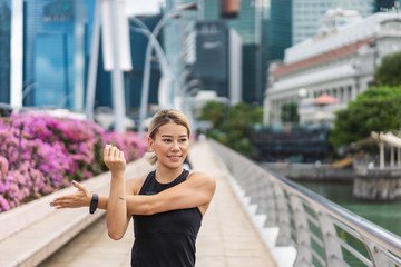 Portrait of Young asian woman doing stretching before running on city