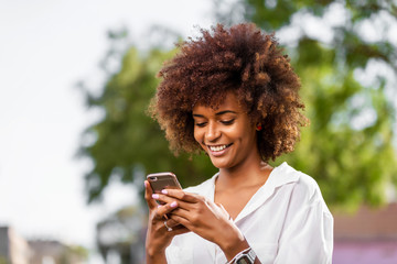 Outdoor portrait of a Young black African American young woman speaking on mobile phone