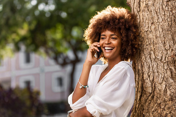 Outdoor portrait of a Young black African American young woman speaking on mobile phone Wall mural