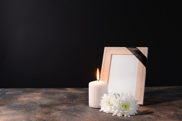Blank funeral frame, candle and flowers on table against black background
