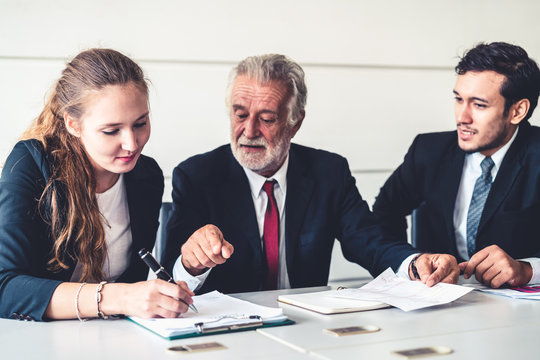 Senior old executive manager working with young businesspeople in office meeting room. Old man is the company leader sitting with secretary and translator. International corporate business concept.