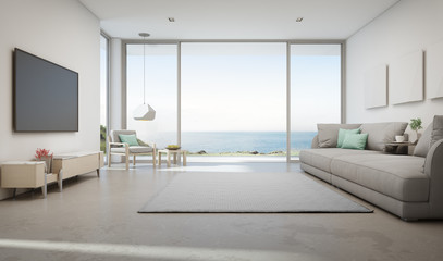 Wall Mural - Sea view living room of luxury summer beach house with large glass door and wooden terrace. TV on white wall against big gray sofa in vacation home or holiday villa. Hotel interior 3d illustration.