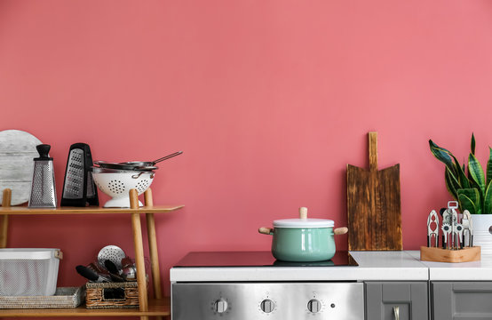 Set of utensils near color wall in kitchen